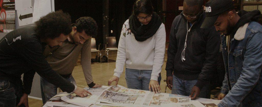 Die Gruppe liest eine auf dem Tisch liegende Zeitung.