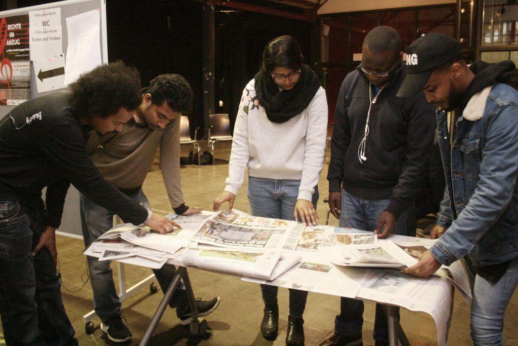 Die Gruppe schaut sich verschiedene auf dem Tisch liegende Plakate an.