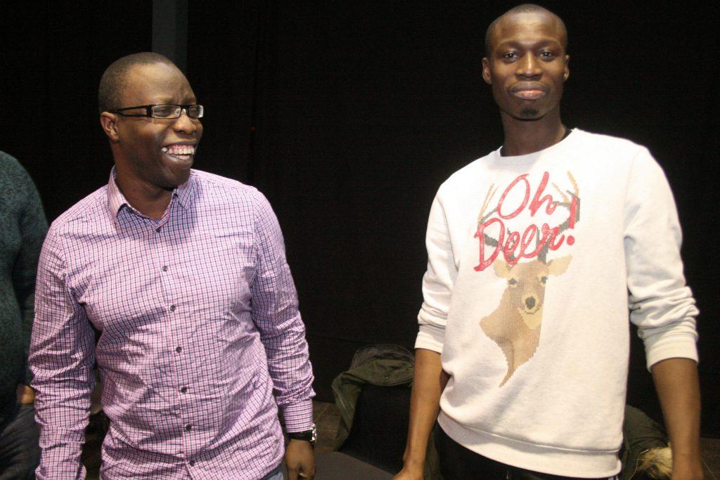 Zwei Männer posieren lächelnd für das Foto.