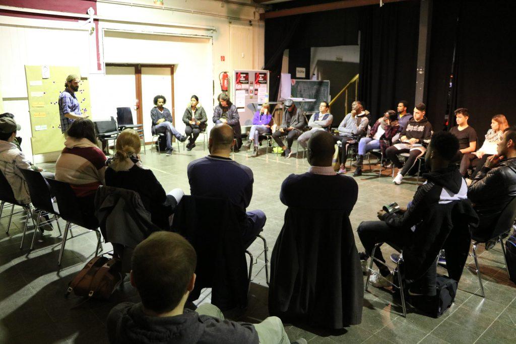 Eine große Gruppe ist in einem Sitzkreis versammelt.