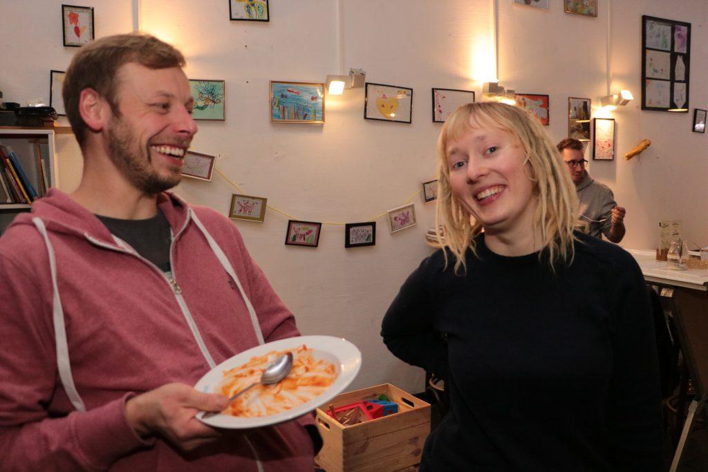 Ein Mann und eine Frau posieren für das Foto, der Mann hält ein Teller mit Essen.