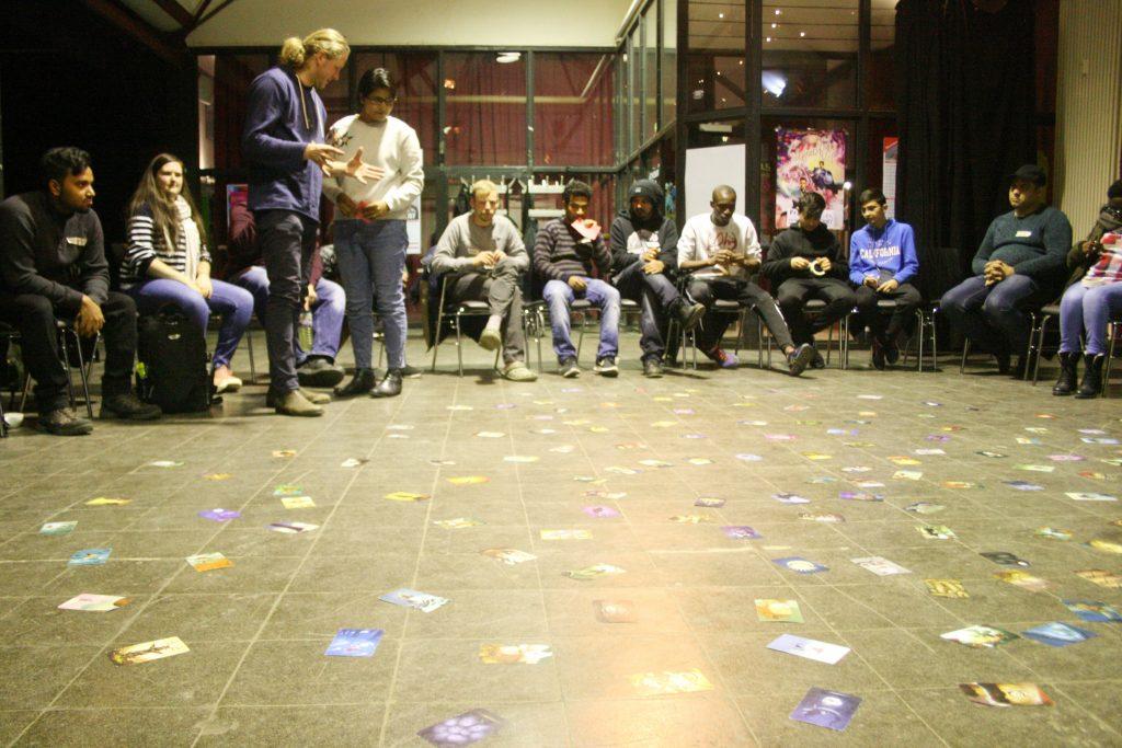 Die Gruppe sitzt um Kreis um sehr viele auf dem Boden verteilte Zettel herum.