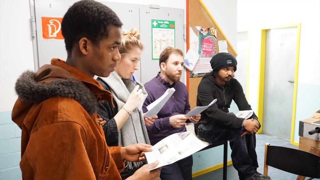 Die Gruppe steht mit Zetteln in der Hand im Halbkreis.