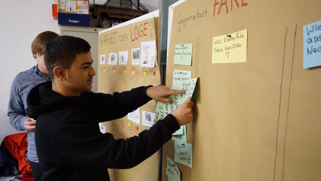 Ein junger Mann pinnt Zettel an eine Pinnwand.