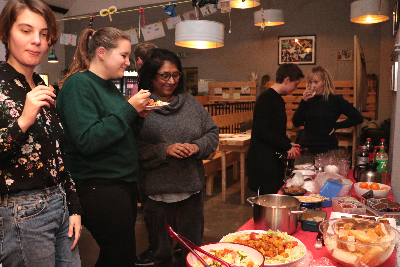 Leute haben sich vor einem großen Tisch voller Essen versammelt.