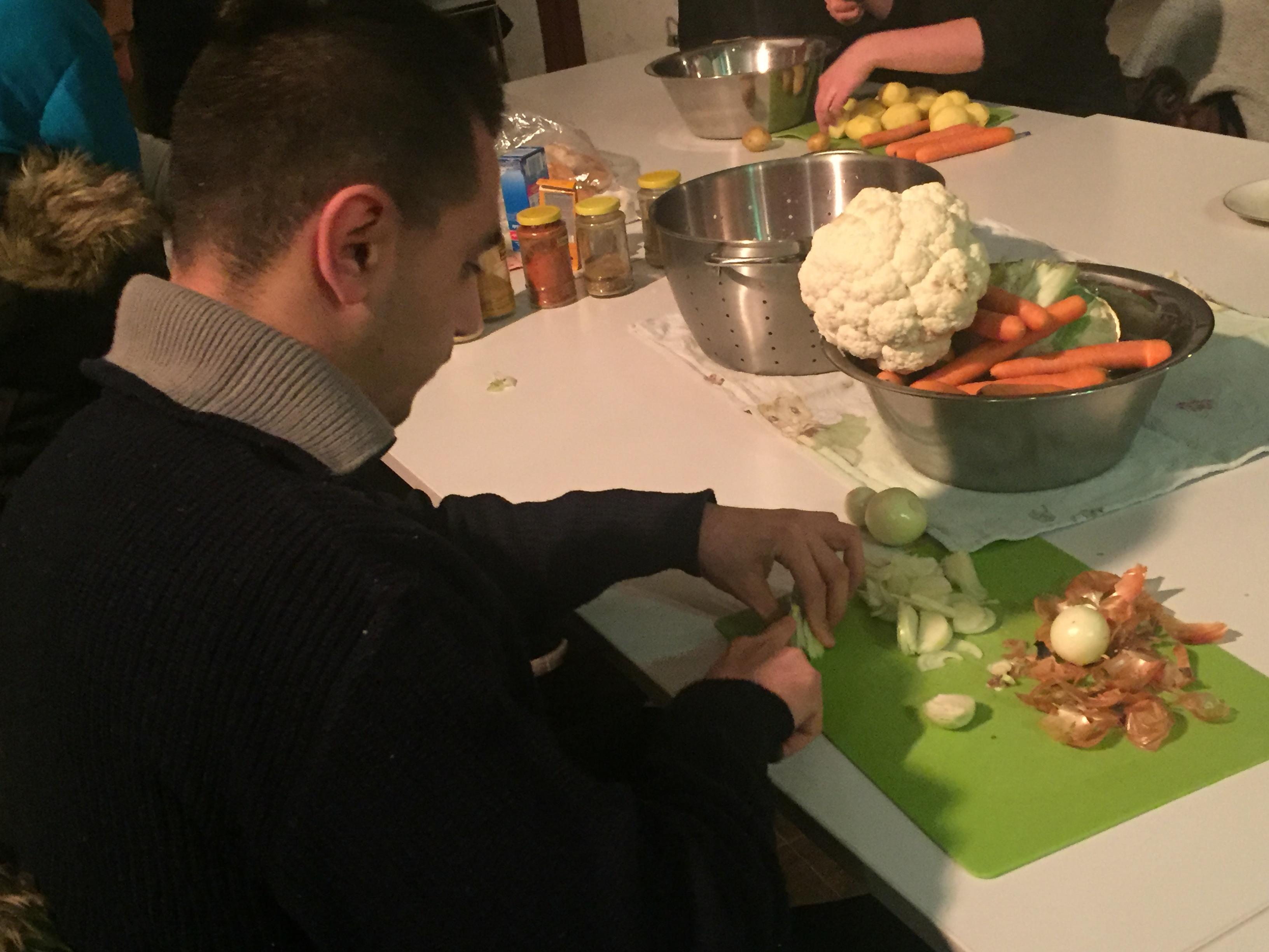 Die Gruppe sitzt am großen Tisch und bereitet Essen zu.