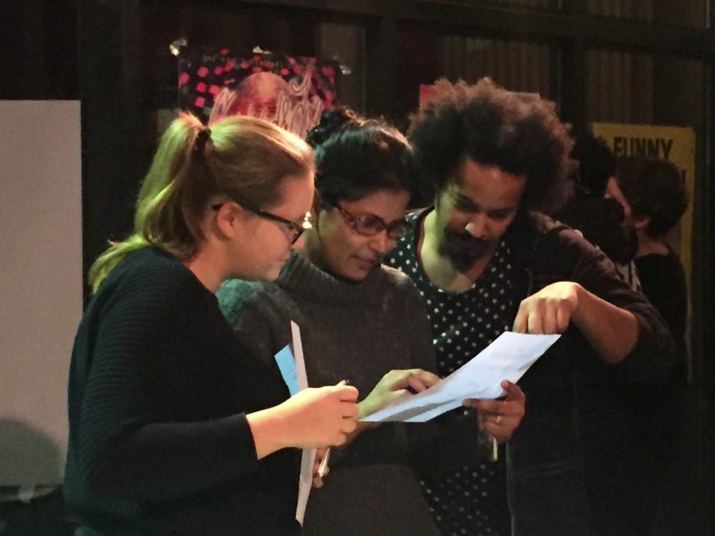 Zwei Frauen und ein Mann lesen einen Zettel.