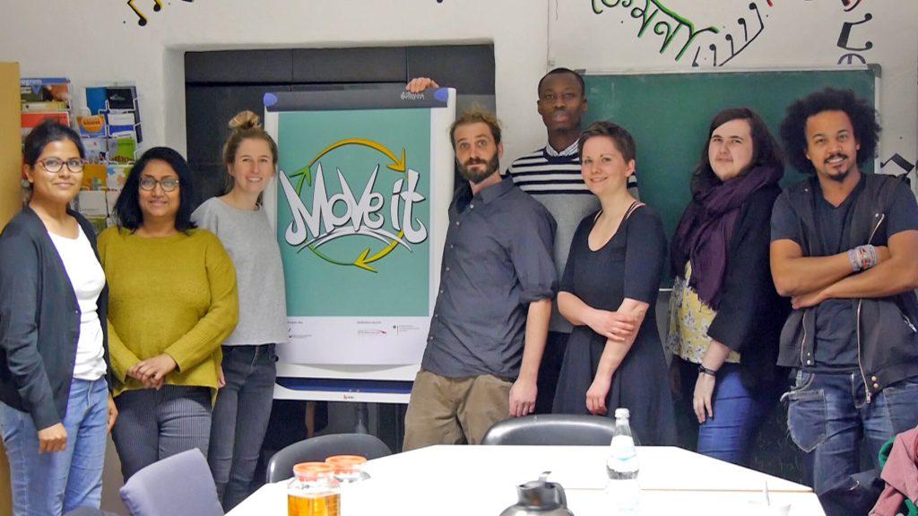 """Leute posieren vor einem Flipchart mit dem """"Move it"""" Logo."""