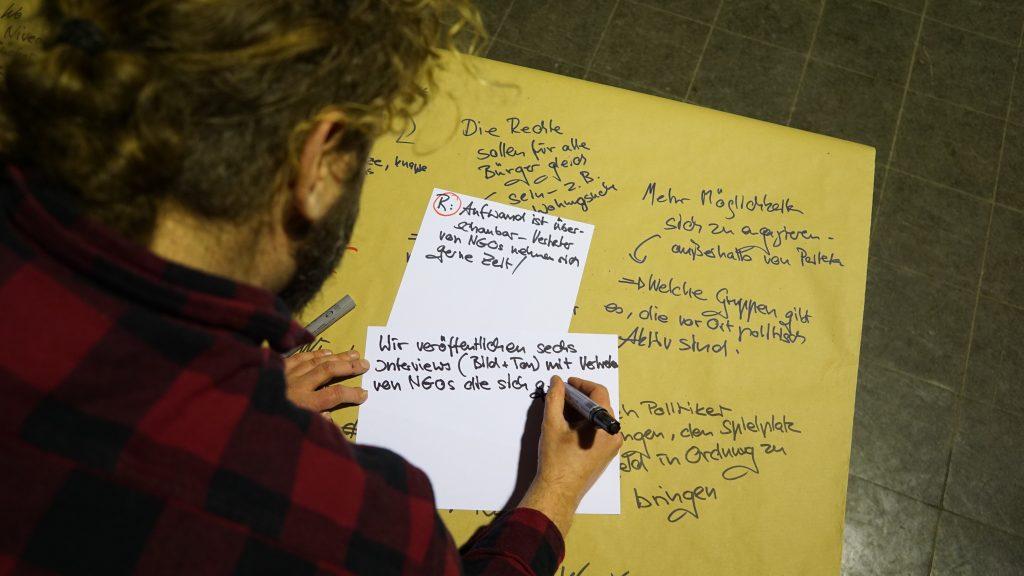 Ein Mann schreibt auf einen Zettel.