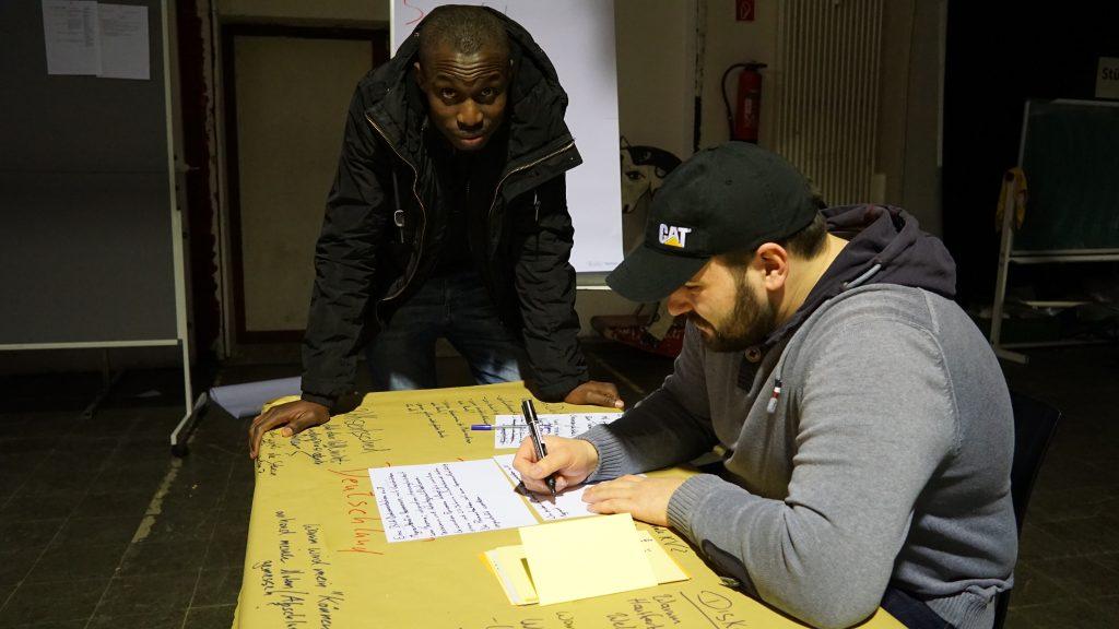 Ein Mann schreibt auf einen Zettel und ein anderer Mann schaut ihm dabei zu.
