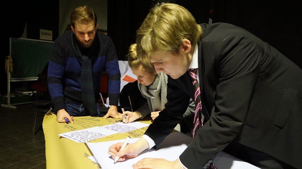 Die Gruppe schreibt auf Zettel.