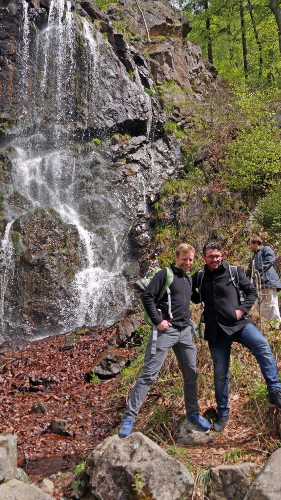 Zwei Männer posieren vor einem Wasserfall.
