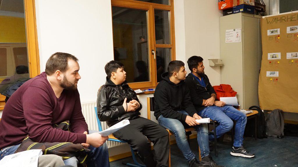 Vier Männer sitzen auf Stühlen und hören zu.