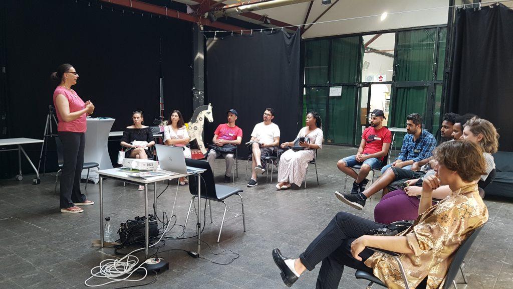 Die Gruppe sitzt in einem Sitzkreis und lauscht einer Präsentation.