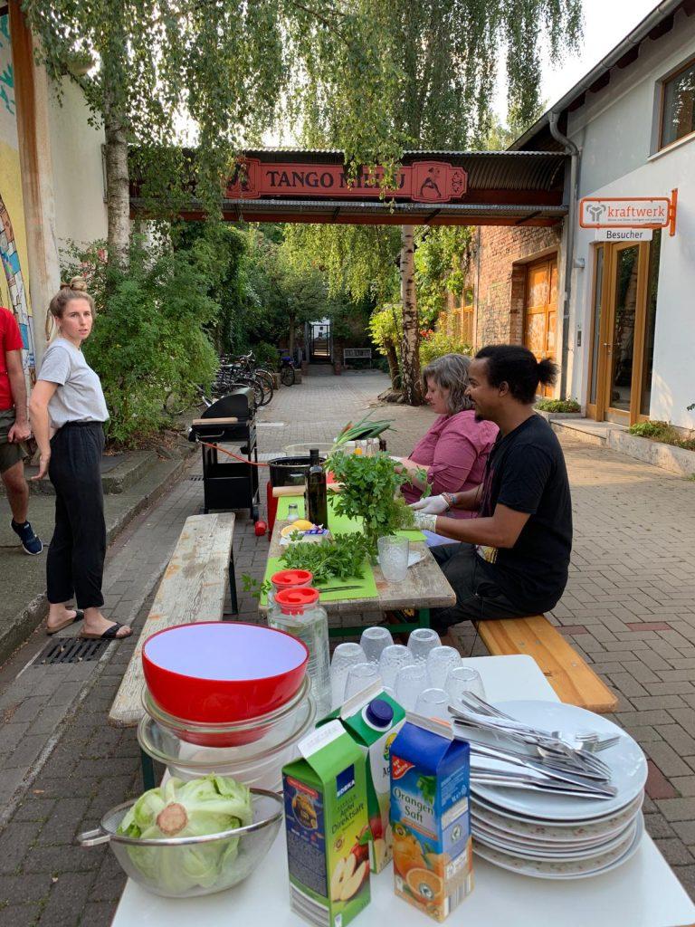 An einem Tisch bereiten ein Mann und eine Frau Essen zu.
