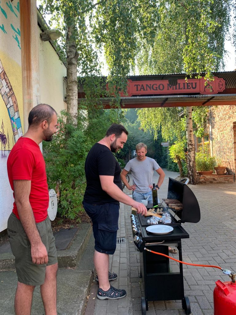 Drei Leute stehen vor dem Grill.