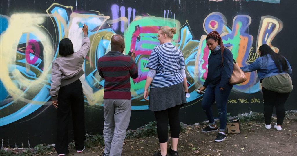 Die Gruppe sprüht ein Graffiti an eine Wand.
