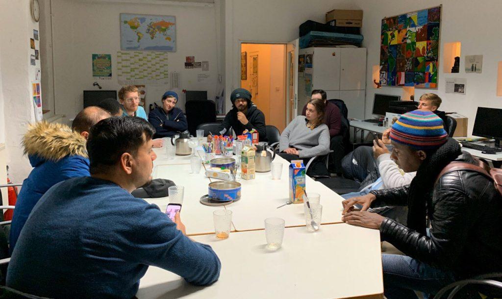 Die Gruppe ist an einem großen Tisch versammelt und diskutiert.