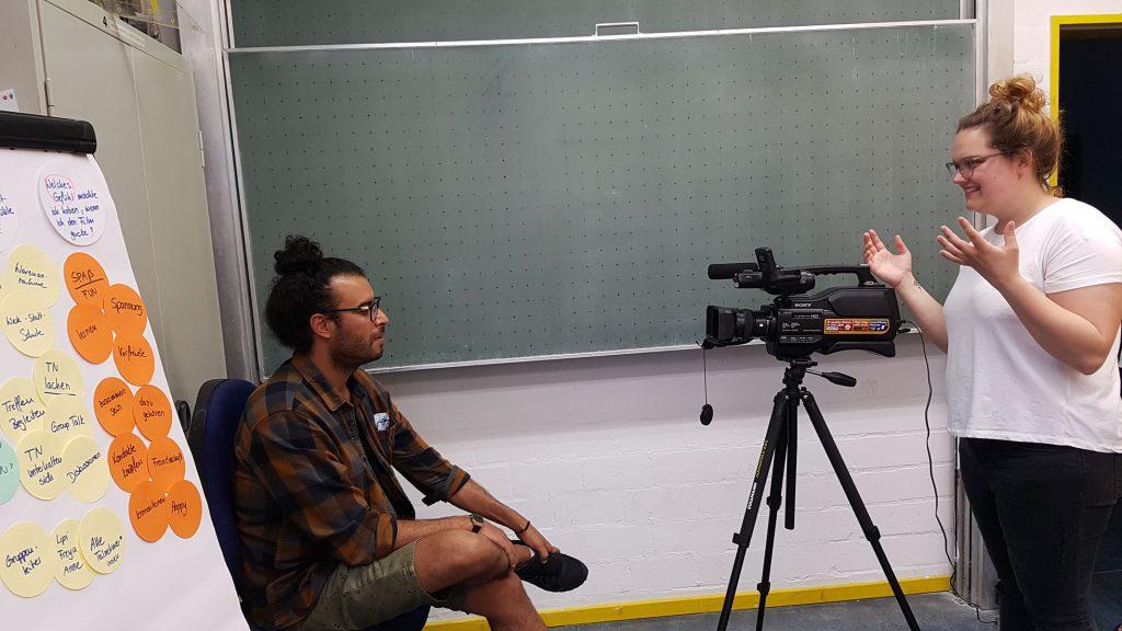 Ein Mann sitzt vor einer Videokamera.