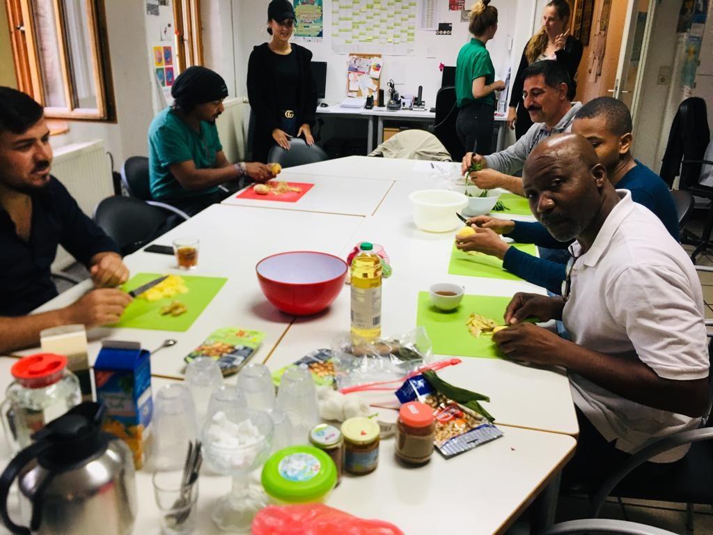 Die Gruppe ist an einem großen Tisch versammelt und bereitet Essen zu.