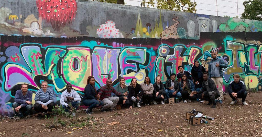 """Die Gruppe posiert vor dem fertigen """"Move it"""" Graffiti für ein Gruppenfoto."""