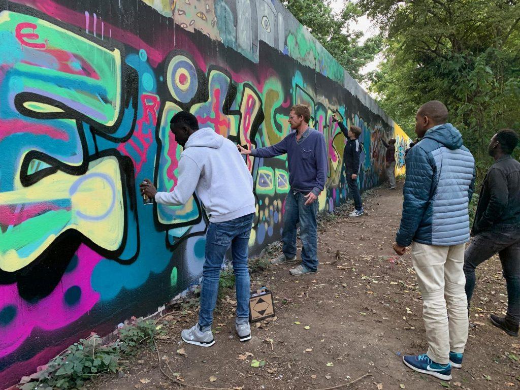 Die Gruppe sprüht fleißig an einem Graffiti.