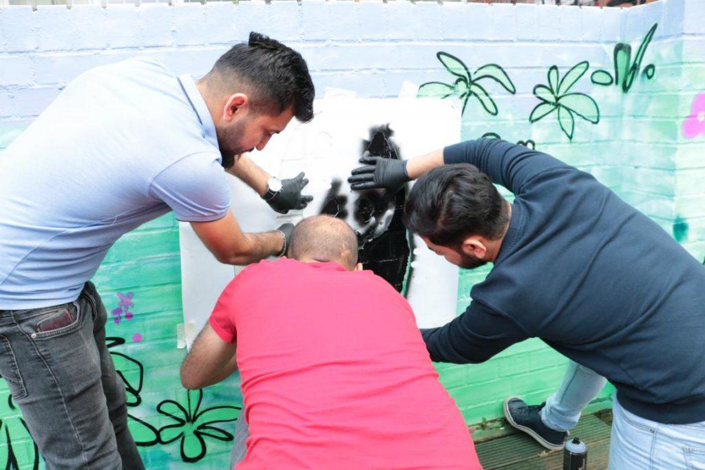 Drei Männer tragen mit einer Schablone Farbe für ein Bild eines Pandabären auf die Wand auf.
