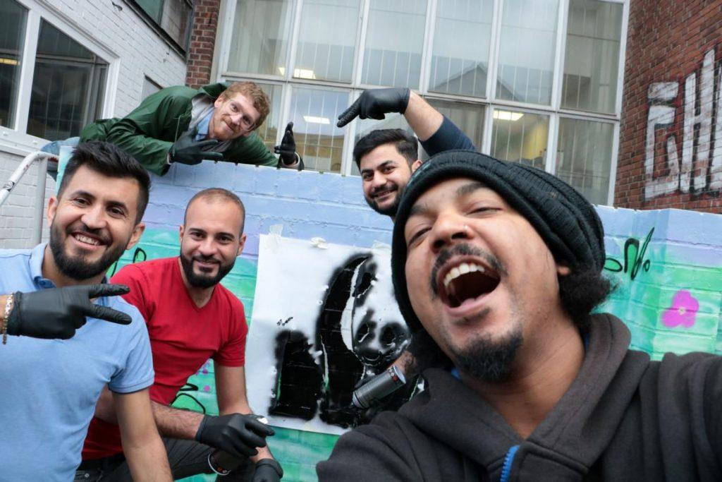 Die Gruppe posiert vor einem Bild eines Pandabären.