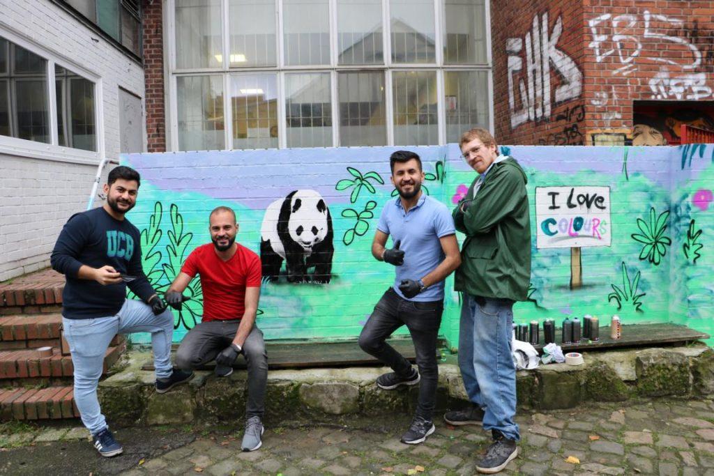 Vier Männer posieren vor einem fertigen Bild eines Pandabären für ein Gruppenfoto.