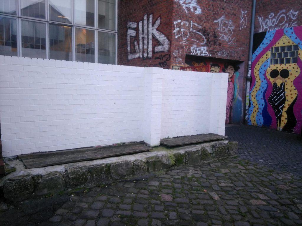 Eine weiße Wand erwartet sehnsüchtig ein Kunstwerk.