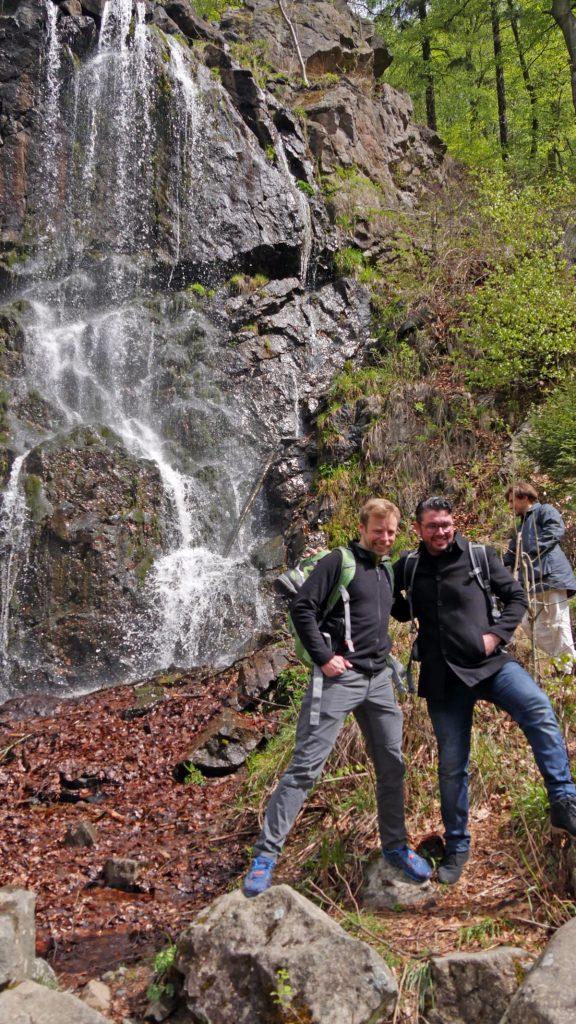 Zwei Männer posieren vor einem kleinen Wasserfall für ein Foto.