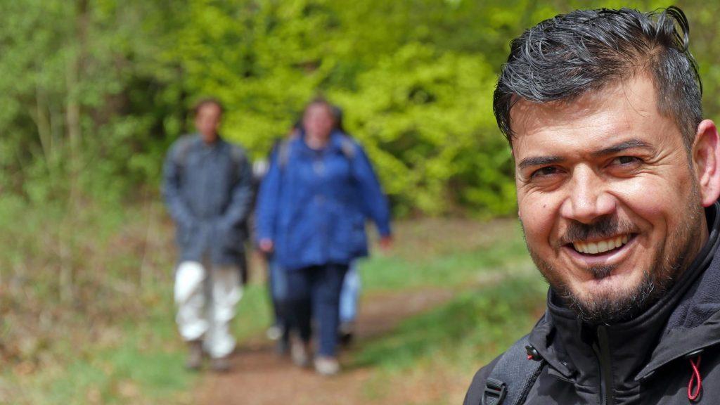 Ein Mann posiert lächelnd für ein Foto, während sich von hinten ein Grüppchen nähert.