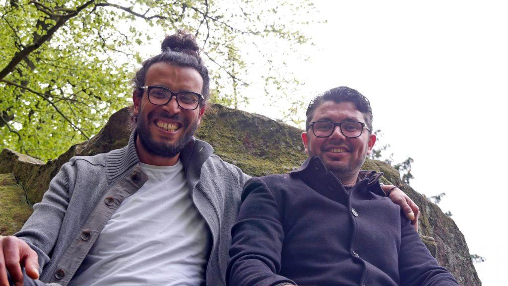 Zwei Männer posieren vor einem Felsen für ein Foto.