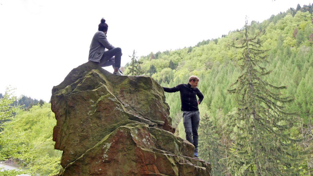 Zwei Männer posieren auf einem moosbewachsenen Felsen.