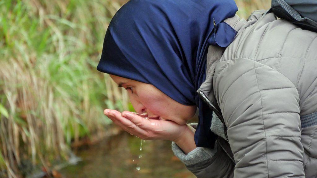 Eine Frau trinkt Wasser aus einem kleinen Bach.