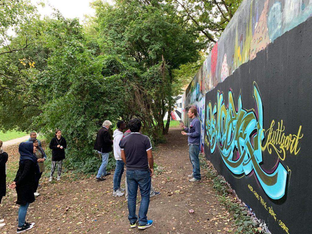 Der Gruppenleiter präsentiert vor einem Graffiti.