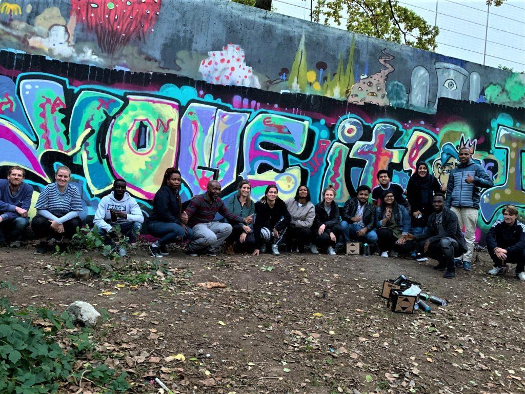 Die Gruppe posiert vor dem fertigen Graffiti für ein Gruppenfoto.