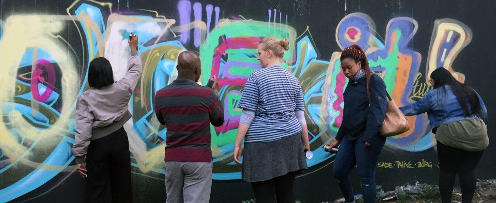 Ein Mann und eine Frau stehen vor einem Graffiti.