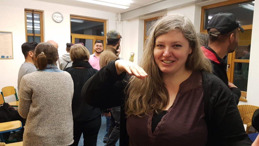 Die Gruppe ist versammelt, eine Frau dreht sich zur Kamera und posiert lächelnd für das Foto.