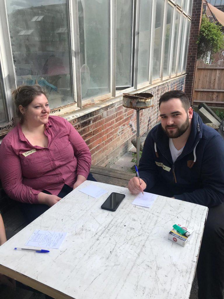 Ein Mann und eine Frau sitzen draußen am Tisch und reden miteinander.