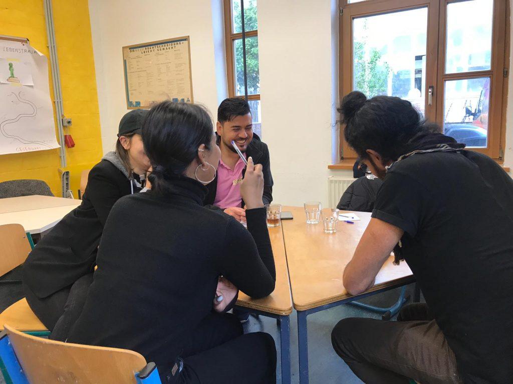 Eine Gruppe sitzt an einem kleinen Tisch und redet.