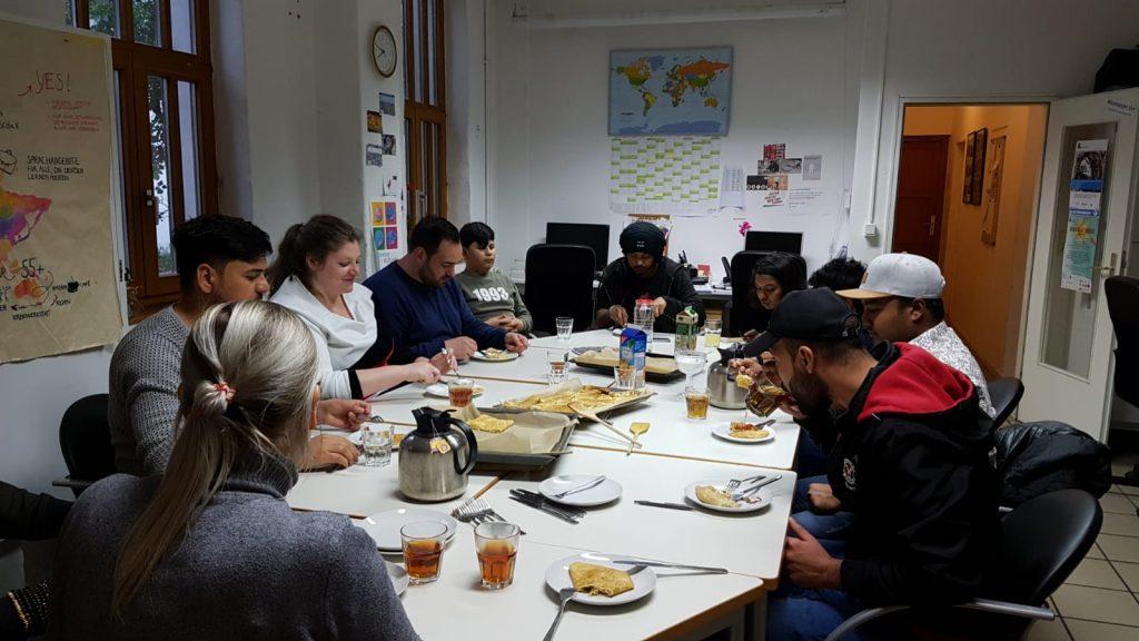 Die Gruppe sitzt am großen Tisch und isst.