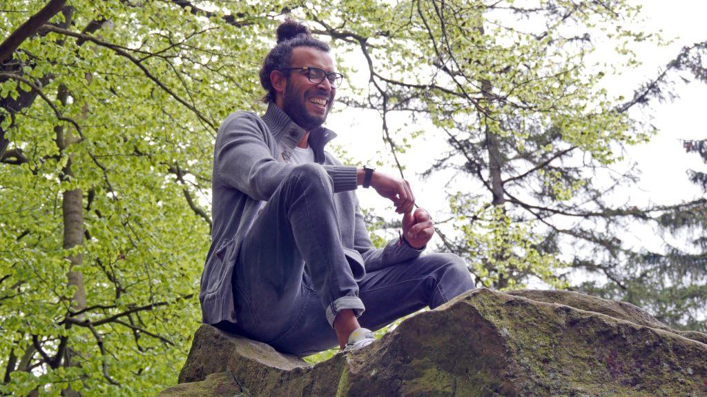 Ein Mann sitzt im Schneidersitz auf einem Stein.