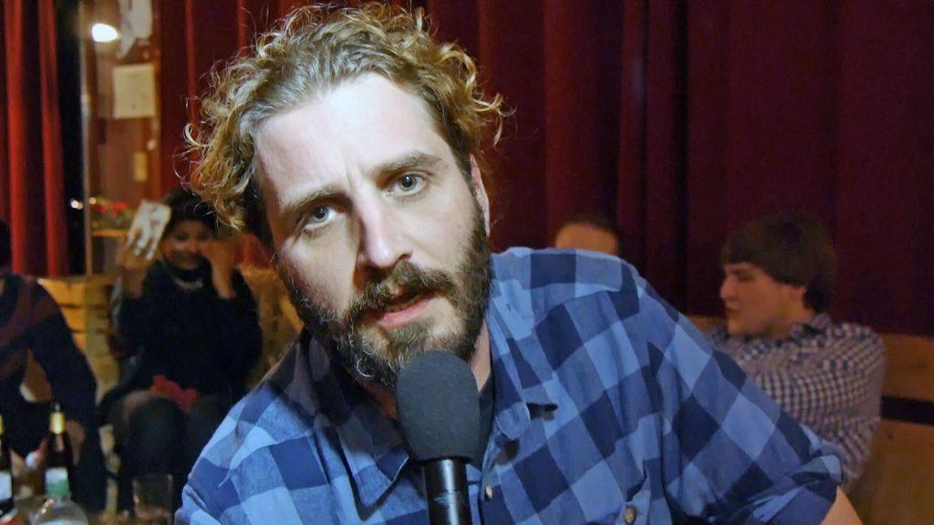 Ein blonder Mann mit krausem Haar und Vollbart.