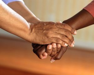 Leute legen ihre Hände aufeinander.