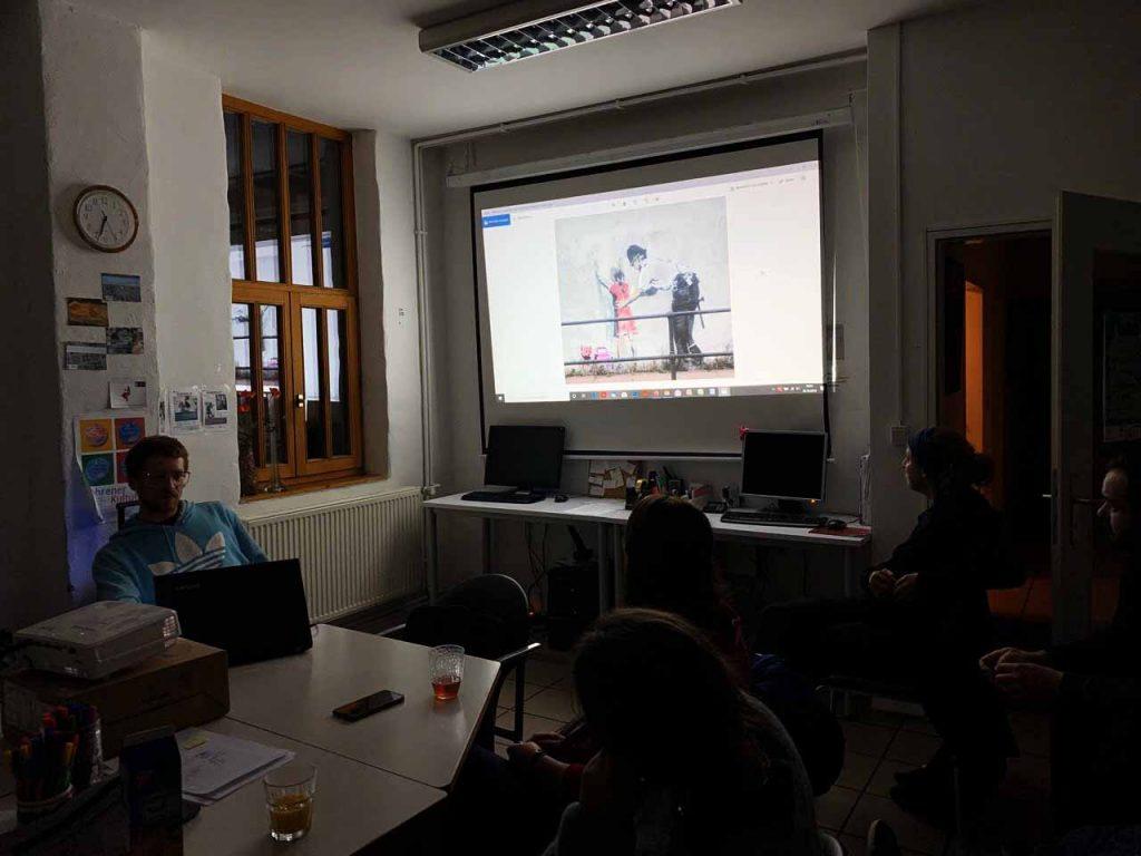 Die Gruppe schaut ein Video auf dem Beamer.