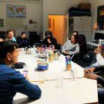 Die Gruppe sitzt an einem Tisch und redet.