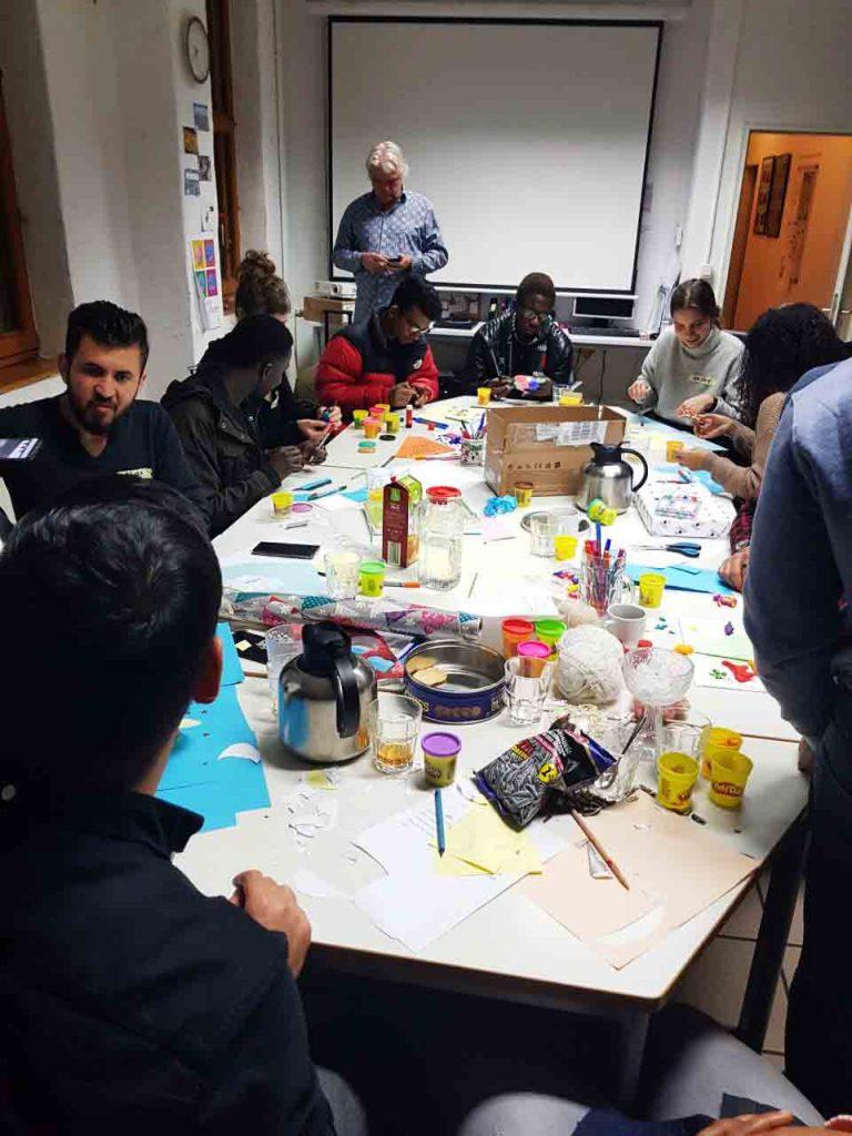 Die Gruppe sitzt an einem Tisch und ist in das Projekt vertieft.