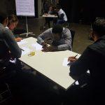 Die Gruppe sitzt am Tisch und schreibt.