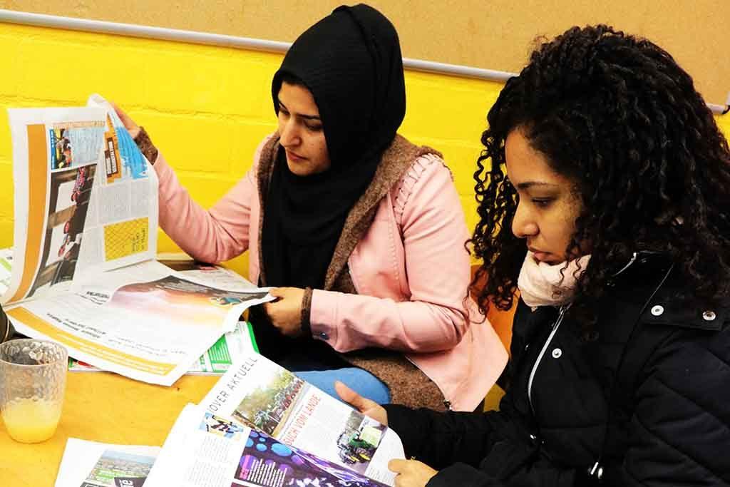 Zwei Frauen haben Zeitungen aufgeschlagen und lesen.